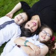 Mother with son and daughter laying in grass — Stock Photo