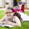 Young Hispanic Girl Reading Outside Smiling — Stock Photo