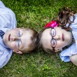 Brother and Sister Laying Down in Grass Eyes Closed — Stok fotoğraf