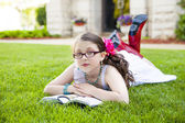 Young Hispanic Girl Reading Outside — Stok fotoğraf