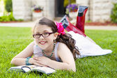 Young Hispanic Girl Reading Outside Smiling — Stockfoto