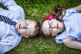 Brother and Sister Laying Down in Grass Eyes Closed — ストック写真