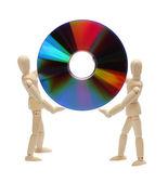 Poupées en bois tenant un cd — Photo