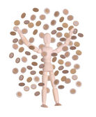 Wooden doll in rain of coins — Stock Photo