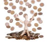 Bambola di legno seduta nella pioggia di monete — Foto Stock