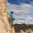 Female climber gripping the rock. - Stock Photo