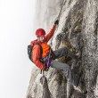 Stock Photo: Climber rappells down cliff.