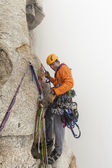 Climber rappells down a cliff. — Stock Photo