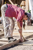 Female carpenter hammers a nail. — Stock Photo
