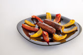 Grilled sausages and colorful peppers — Stock Photo