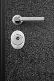 Black front door with lock and handle — Stock Photo