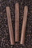 Three cigar on coffee beans background — Stock Photo