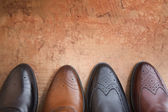 Four men shoe close up on a background of vintage wall — Stock Photo