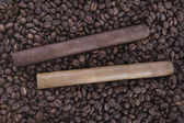 Two cigar on coffee beans background — Stock Photo