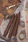 Three cigars and a compass on the background of old maps — Stock Photo