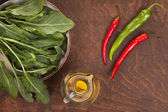 Pepper, olive oil and green leaves  — Stock Photo