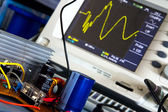 DC / DC converter and the switching waveform on the oscilloscope — Stock Photo