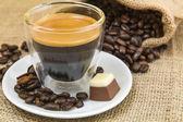 Fresh espresso coffee with crema with pralines — Stock Photo