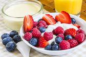 Sweet raw berries with orange juice on coverlet — Stock Photo