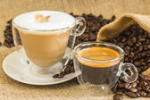 Cappuccino and espresso in glassy cups with roasted coffee beans — Stock Photo