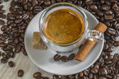 Fresh espresso coffee with sugar, cinnamon and lot of beans — Stock Photo