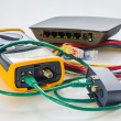 Network tester and small switch with various color RJ45 cables c — Stock Photo #50526879