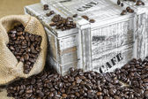 Burlap bag filled with coffee beans beside old wooden box — Stock Photo