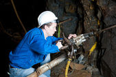 Miner underground with drill — Stock Photo