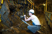 Underground miner drilling into rock — Stock Photo