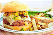 Juicy hamburger with fresh salsa topping — Stock Photo