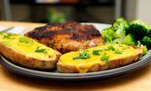 Twice baked potato smothered with cheese and green onions with a — Stock Photo