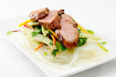 Grilled pork tenderloin with fresh sauteed vegetables over mango — Stock Photo