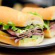 Deli style roast beef sliced on a submarine roll with heirloom t — Stock Photo
