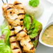 Grilled chicken on bamboo skewers with a peanut dipping sauce — Stock Photo