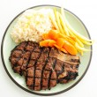 Rib steak grilled to perfection with creamy risotto, carrots and — Stock Photo