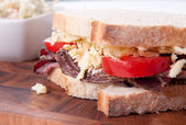 Sliced roast beef sandwich with cheese and tomato and cole slaw — Stock Photo