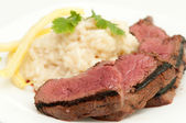 Medium rare beef tenderloin grilled to perfection with creamy risotto and yellow string beans — Stock Photo
