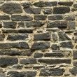 Seamless black ashlar old stone wall texture — Stock Photo