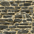 Seamless black ashlar old stone wall texture - Stock Photo