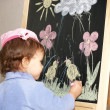 The little girl draws color pieces of chalk on an easel - Stock Photo