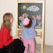 Royalty-Free Stock Photo: Mother teaches the small daughter to draw color pieces of chalk on an easel