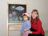 Mother teaches the small daughter to draw color pieces of chalk on an easel — Stock Photo