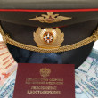 Stock Photo: Military peak-cap and pension certificate