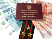 The pension certificate and shoulder strap against money — Stock Photo