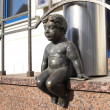 Stock Photo: Lithuania, Klaipeda. Sculpture of naked boy sitting on por