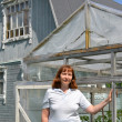 Stock Photo: Womof average years stands near greenhouse