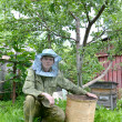The young beekeeper from swarms to it on an apiary — Stock Photo