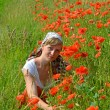 The young woman among red poppies — Stock Photo