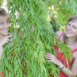 Two young women look because of willow branches — Stock Photo
