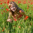 The young woman smiles among red poppies — Stock Photo